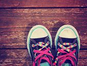 picture of angle  - a wide angle photo of a pair of generic looking shoes like converse sneakers with pink shoe laces on a vintage wooden background toned with a retro vintage instagram filter app - JPG