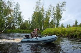 picture of hunter  - Hunter goes in motor boat on the river - JPG