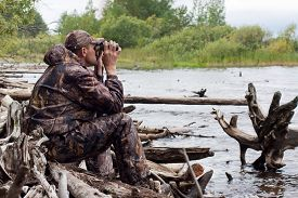 stock photo of hunter  - hunter looking through binoculars on the river - JPG