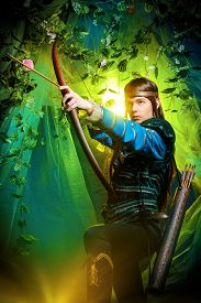 foto of bow arrow  - Portrait of a male elf with a bow and arrows in a magical forest - JPG