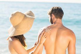 stock photo of sun tan lotion  - pretty brunette putting sun tan lotion on her boyfriend at the beach - JPG