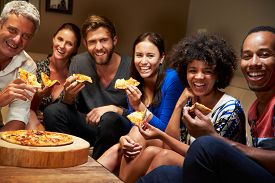 stock photo of social housing  - Group of adult friends eating pizza at a house party - JPG
