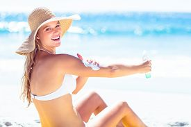 foto of sun tan lotion  - Pretty blonde woman spreading sun tan lotion on her arms at the beach - JPG
