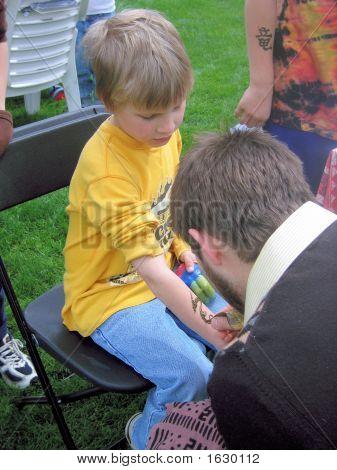 Boy getting temporary henna tattoo