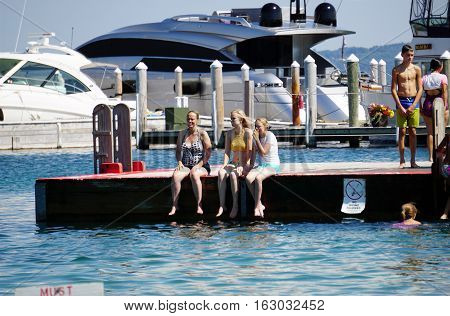 HARBOR SPRINGS, MICHIGAN / UNITED STATES - AUGUST 3, 2016: Swimmers sit on the edge of a raft at the Zorn Park Public Beach near downtown Harbor Springs.