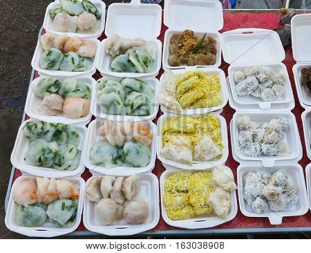 steamed chives dumplings,Thai Coconut muchkins, tapioca pork and mung bean rice-crepe in foam package box for sell in the market