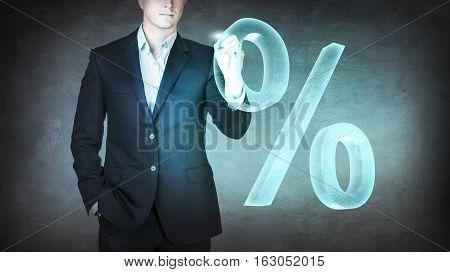 Businessman pushing big virtual percent over blue background.