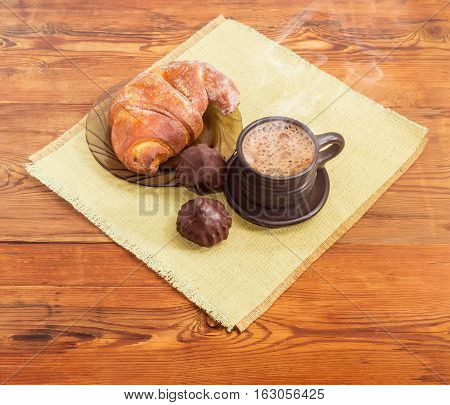 Freshly brewed coffee latte in a black ceramic cup croissant on a glass saucer and two chocolate truffles on a napkin on an old wooden surface