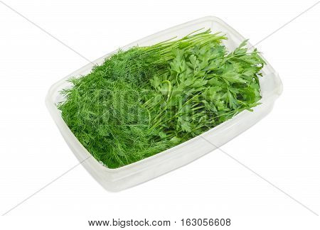 Bunches of a fresh parsley and dill in a plastic tray on a light background