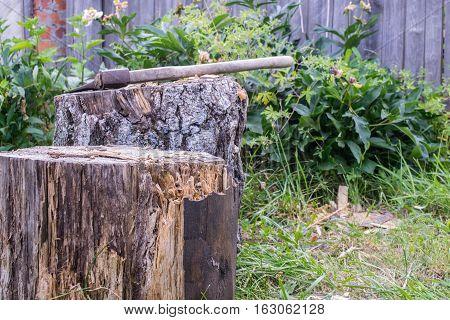 Axe on log near wooden garden fence