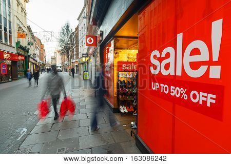 NOTTINGHAM ENGLAND - DECEMBER 26: Boxing Day sales poster and sales shoppers on Clumber Street in Nottingham Britain. In Nottingham England. On 26th December 2016.