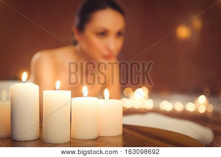 Calm young girl is enjoying her vacation. She is lying at spa with relaxation. Focus on candles