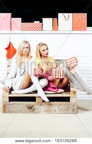 Pretty girls or two sexy cute women with blond hair in home wear read book on wooden pallet sofa with shopping bags and gift boxes on white brick wall
