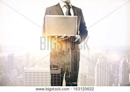 Businessman holding laptop on abstract city background with sunlight. Communication concept. Double exposure