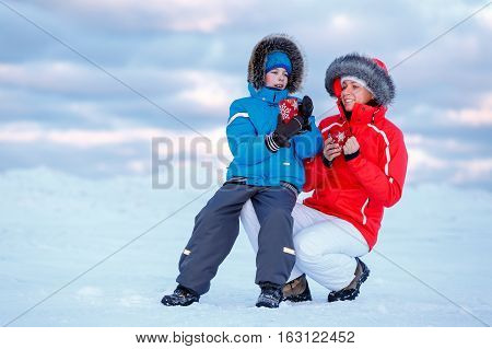 Cute little boy and his mother drinking hot tea on icy beach, winter family holiday