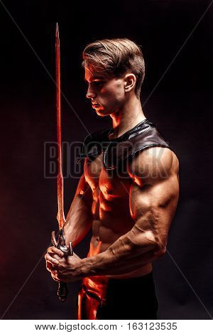 Portrait of sexy muscular concentrated man holding sword.