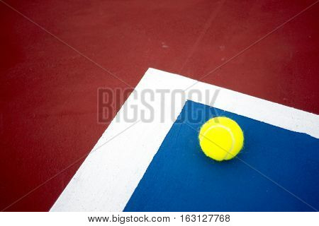 The tennis ball on the tennis court.