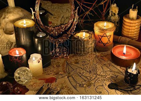 Mystic still life with demon manuscript, mirror and black candles. Halloween concept. Esoteric objects on table. There is no foreign text in the image, all symbols are imaginary and fantasy ones