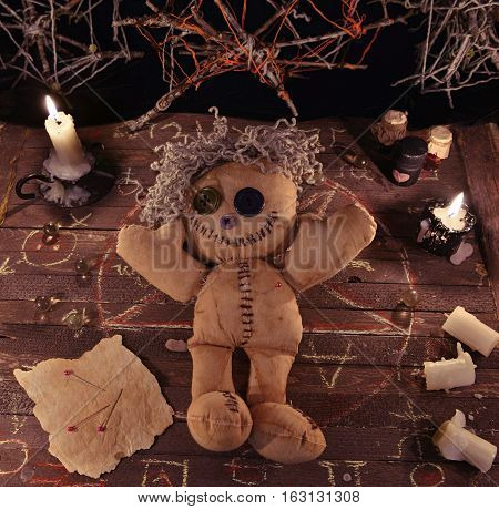 Voodoo ritual with doll, candles and vintage objects on wooden table. Halloween background, black magic rite or spell with occult and esoteric symbols