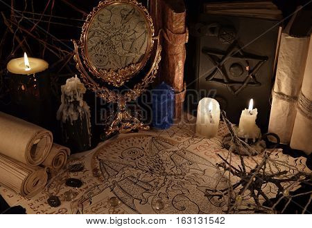Mystic still life with magic mirror, demon paper and blue crystal. Halloween concept. Esoteric objects on table. There is no foreign text in the image, all symbols are imaginary and fantasy ones