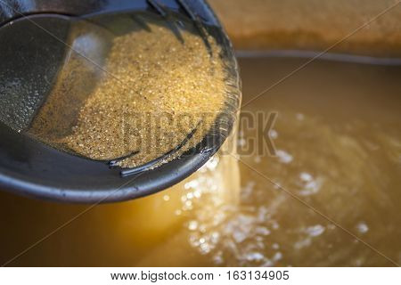 Close up of gold panning pan with sifting sand. Shallow depth of field with focus on sand flowing over edge of pan into water.