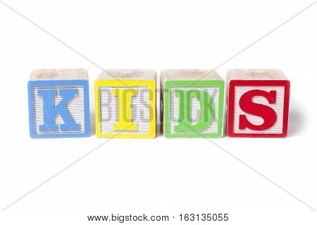 Isolated alphabet blocks on white background spelling out Kids.