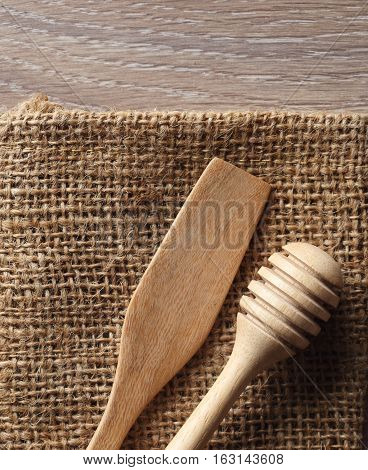 Wooden dipper kitchenware on sack and wood board background