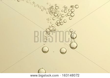 Golden fizz bubbles over a blurred background