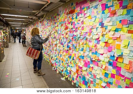 New York, United States of America - November 21, 2016: People looking at sticky post-it notes on wall in Union Square subway station which were set up as protest against presidential election results