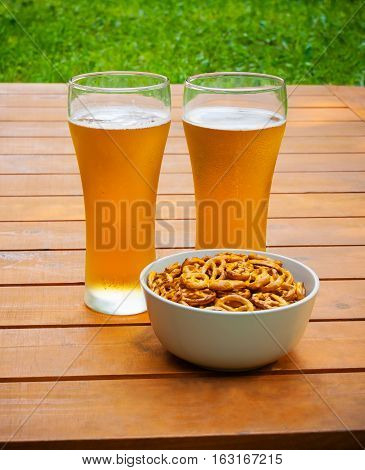 Glasses of beer and bowl of pretzels on wooden table