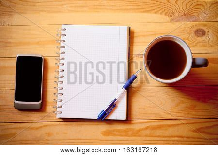 Notebook tea cup and smart phone on wooden background