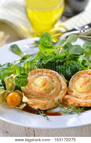 Baked hearty puff pastry snacks with smoked salmon, cream cheese and fresh herbs on lambs lettuce
