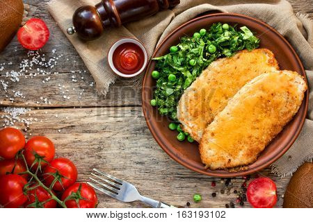 Chicken schnitzel with or cordon bleu with green salad and cherry tomatoes in a rustic style on the old wooden background top view blank space for text