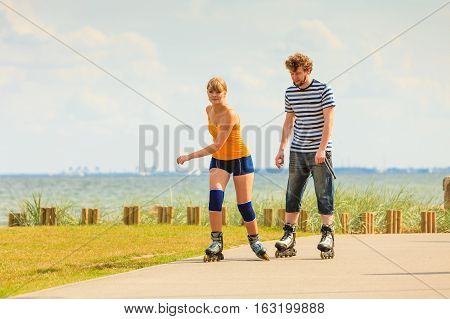 Active lifestyle people and freedom concept. Young fit couple on roller skates riding outdoors on sea coast woman and man  enjoying time together