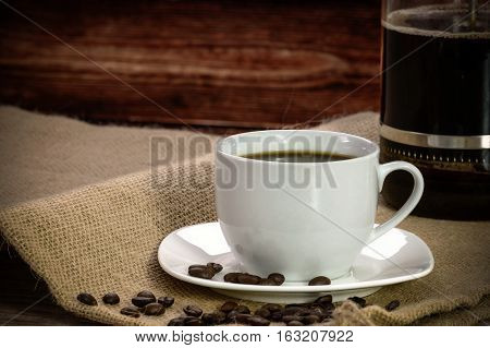 Cup of coffee with roasted beans and coffee maker on a burlap sack.