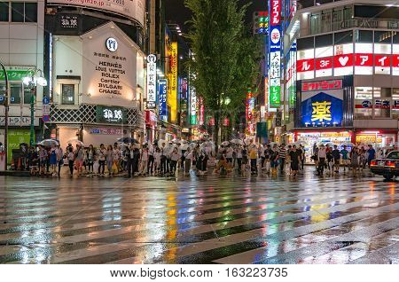 Tokyo Japan - August 29 2016: People at pedestrian crossing in Kabukicho Ichibangai with world famous fashion brand stores on the background. Text in Japanese advertises clothing goods and services