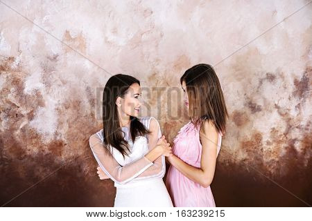 Two adult brunette look alike sisters looking at each other and smiling