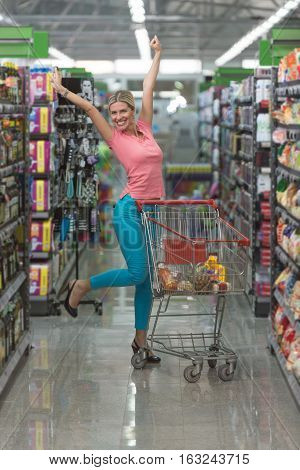 Happy Woman Driving Shopping Cart In Supermarket