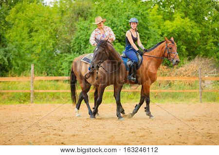 Western ride relations through passion concept. Cowgirl and woman jockey in helmet riding on horses coutryside meadow sunny day.