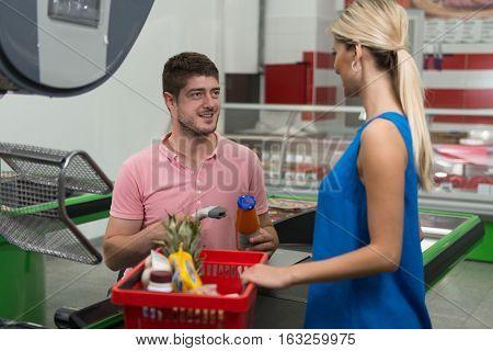 Customer Using Credit Card At Supermarket Checkout