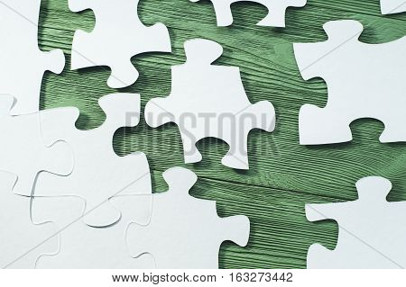 The concept of logical thinking. White jigsaw puzzle on a wooden background flat lay. Business concept with white jigsaw puzzle on green wooden background. Placing missing a piece of puzzle.