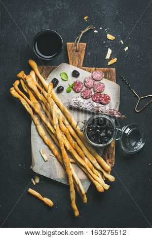 Wine and appetizers set. Italian Grissini bread sticks, dry cured pork meat sausage, black olives in jar on rustic wooden serving board and red wine in glass over dark stone background, top view