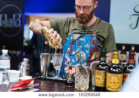 Kyiv, Ukraine - 30 october, 2016: Barman festival. Handsome bearded hipster barman with long beard and mustache with funny face holding shaker and making alcoholic cocktail