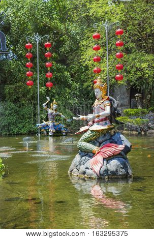 PHUKET THAILAND - CIRCA MAR 2015: Mythological characters adorn the artificial pond. In Thailand you can see lot of bright and lovingly made heroes of epic