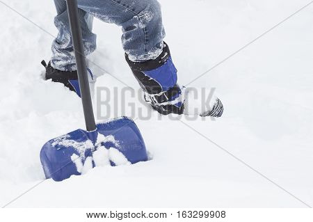 horizontal image of the bottom torso of a man wearing winter boots and in jeans walking through heavy snow with his shovel in winter time.