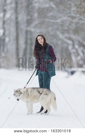Portrait of Lovely Caucasian Brunette Woman Along With Her Husky Dog. Walking Together Outdoors in Snowy Winter Forest.Vertical Image composition
