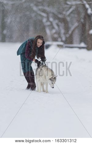 Young Caucasian Brunette Girl Walking With Husky Dog Outside in Winter Snowy Forest.Vertical Image Orientation