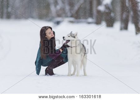 Human and Pet Relationships. Caucasian Brunette Woman Playing with Husky Dog Outdoors in Park. Horizontal Shot