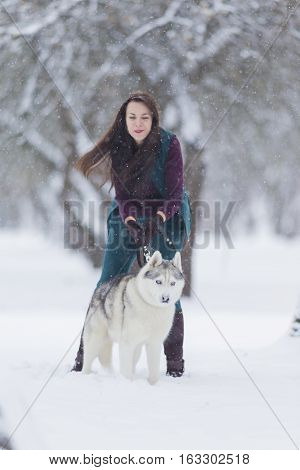 Happy Smiling Caucasian Brunette Woman and Her Husky Dog. Playing Outdoors in Winter White Forest Together. Vertical Image