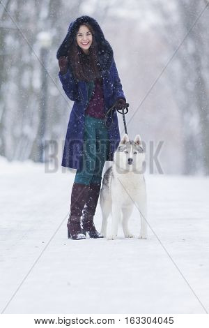 Positive Caucasian Woman Airing Her Husky Dog. Walking In Winter Forest Outdoors.Vertical Image Composition